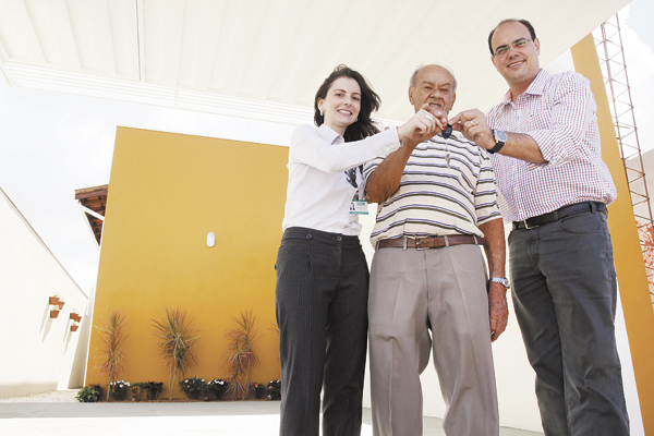 Oswaldo Alves recebe de Beatriz Avila, do GCN, e de Tony Cintra, da Mazza Imóveis, as chaves da casa que ganhou (Foto: Wilker Maia/ Comércio da Franca)